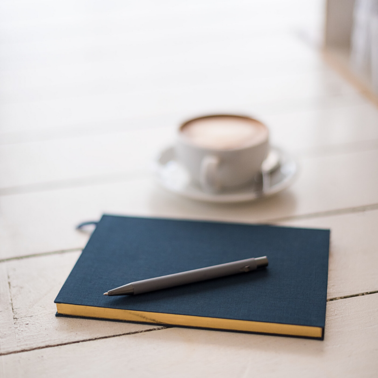 image of blue journal with pen on top and coffee in the background