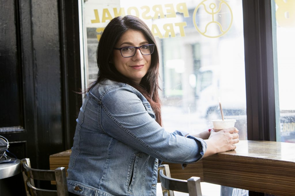 tara newman in denim jacket at a coffee shop