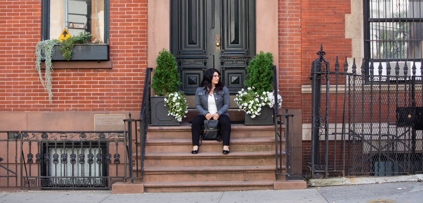 tara newman sitting outside on steps in front of black door